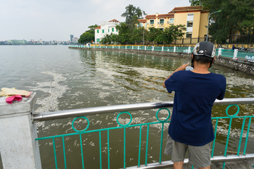 The man taking photo of mass dead fish on West Lake ( Ho Tay ), Hanoi, Vietnam