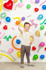 boy on a white background with colorful balloons. boy raising his hands up on a white background with balloons