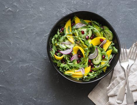 Tropical mango, avocado, cucumber, arugula salad. Delicious healthy vegetarian food. On a dark background, top view