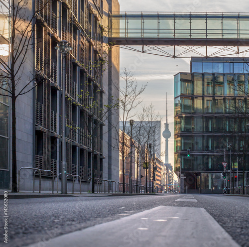 Eine menschenleere strasse in berlin der fernsehturm wird durch moderne architektur eingerahmt for Berlin moderne architektur