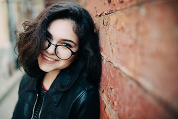 Beautiful happy hipster girl goes in the city. Closeup of trendy girl face.