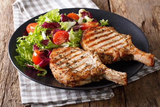 Grilled pork steak with bone, fresh vegetable salad close-up. Horizontal