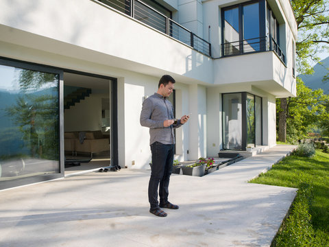 man using mobile phone in front of his luxury home villa