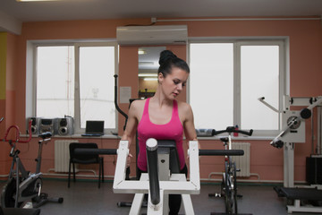 Beautiful girl is exercising in the fitness club on the simulator.