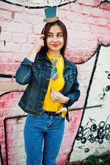 Beautiful fun teenage girl with hat and tie on stick wear yellow t-shirt, jeans near graffiti wall.
