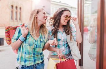 Happy young women in shopping. Consumerism, fashion, lifestyle concept