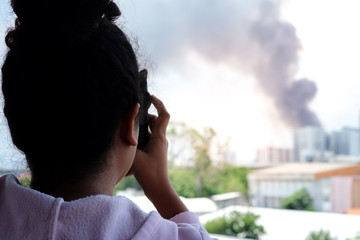 Asian women are using a smartphone to photograph a new fire incident. up to social network