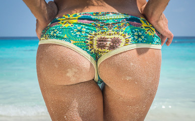 Woman buttocks on a tropical beach background