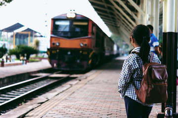 Cute girl in train station waiting to travel. Summer holiday and travel concept.