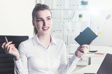 Cheerful blond woman with notebook