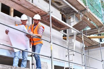 Architekten/ Bauleitung auf einer Baustelle beim Neubau eines Hauses auf dem Baugerüst