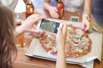 Woman taking photo of pizza with smart phone