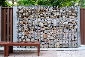 Natural stone wall, versatile in horticulture and slope stabilization; Wire basket filled with broken stones; Building materials industry