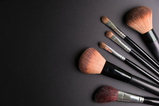 Set of flat top view of various professional female cosmetics brushes for makeup isolated on black background, Cosmetics concept, Makeup concept, Copy space image for your text, Flat lay.
