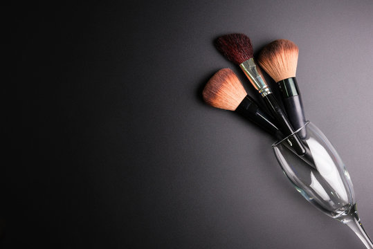 Set of flat top view of various professional female cosmetics brushes for makeup and Wine glass isolated on black background, Cosmetics concept, Makeup concept, Copy space image for your text.