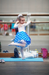 Little ballerina practicing in a dance class. Child girl posing at ballet barre in a dance class. Preschool child taking dance lessons. Ballet school. Shallow depth of field. Selective focus.