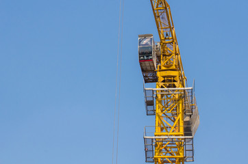 yellow construction tower crane with blue sky