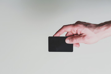 Man's hand is holding a business card on white background