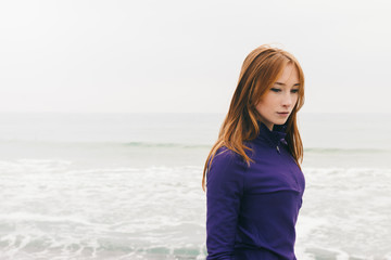 Pensive beautiful young red-haired girl on the beach on a cloudy day