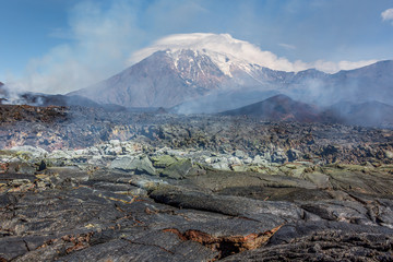 The new lava flow and sulfuric field from a crater on the slopes of volcanoes Tolbachik (on background) - Kamchatka, Russia