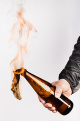 Glass bottle, the so-called Molotov cocktail in the hand of the activist. Isolated on a white background.