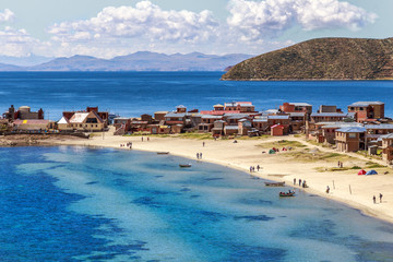 Blue water and coast of Titicaca lake, boats, walking people and bolivian village at Incas Island of the Sun, Bolivia, south America