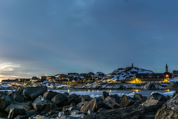 Nuuk city old harbor sunset view with stones and icebergs, Greenland