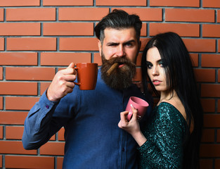 bearded man and pretty sexy woman with cigar, tea cups