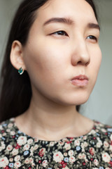 A beautiful Chinese girl thinks through a plan for revenge, screwing up her eyes and squeezing her lips
