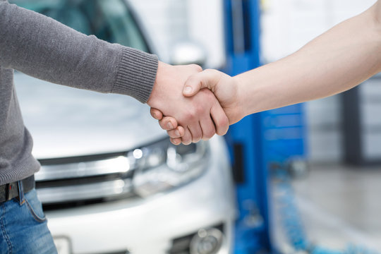 Mechanic shaking hands with his client