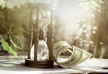 Time is money business philosophy. Hourglass with dollar bills.
