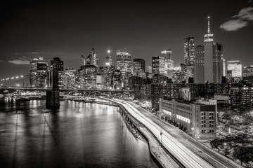 Fotomurales - Lower Manhattan skyscrapers and Financial District. The Black & White elevated night view includes the West tower of the Brooklyn Bridge, East River and traffic light trails on the FDR Drive. New York