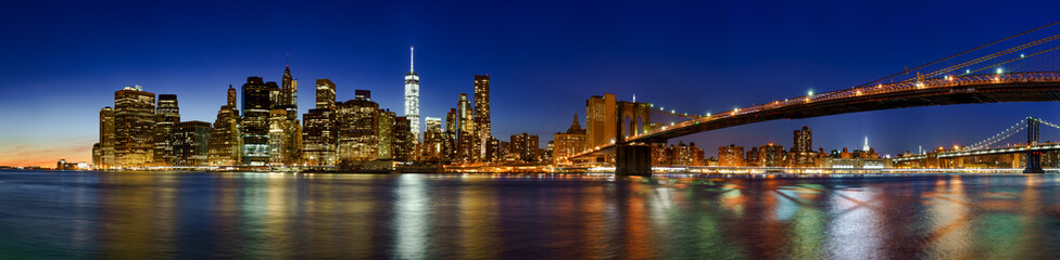 Fotomurales - Panoramic view of Lower Manhattan Financial District skyscrapers at twilight with the Brooklyn Bridge. New York City