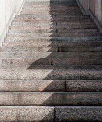 A granite staircase is half in the shade