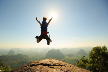 Spoed Fotobehang Luchtsport cheering successful young woman hiker jumping on mountain peak