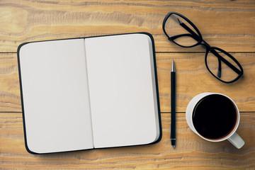 Desktop with notepad, mug and glasses