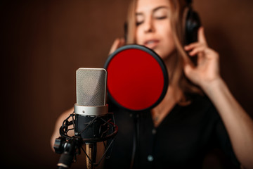 Female singer in headphones against microphone