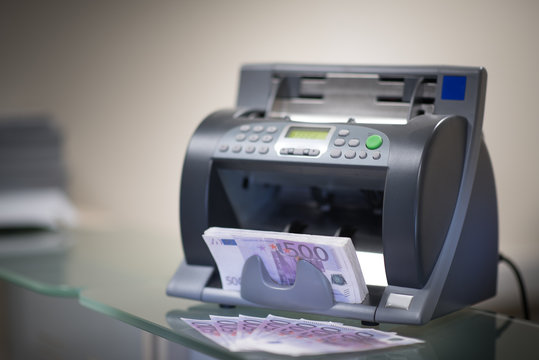 Banknote counter is counting euro banknotes on a blured background