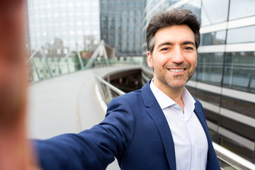 Attractive middle aged business man taking selfie on the way to office - business concept