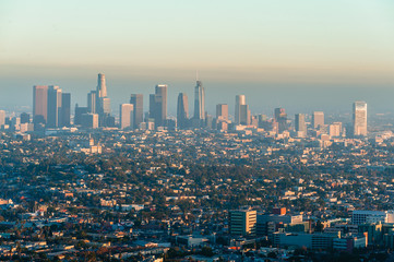 Los Angeles cityscape at evening from Griffith Observatory balcony. View to the skyscrapers in downtown Los Angeles with a straight streets and roads. Smoke in the air in Los Angeles