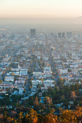 Los Angeles cityscape at evening from Griffith Observatory balcony. View to the pacific ocean with a straight streets and roads. Smoke in the air in Los Angeles
