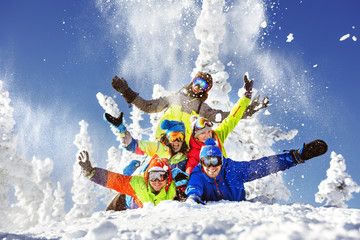 Group of five happy snowboarders and skiers
