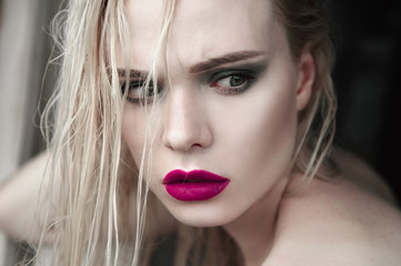 Portrait of beautiful girl model with pink lips and blue eyes with leather belt on her neck, fresh clean highlighted skin. Fashion retouched close up shot. Sad depressed mood