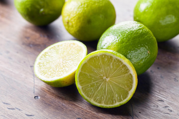 Group of whole and cut fresh limes on a wooden table .