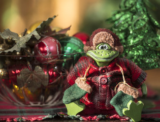 Green frog dressed in winter coat sitting in front of xmas tree and bowl of decorations