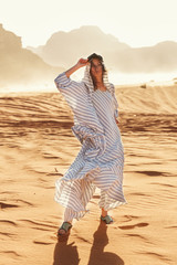 Stylish girl in white dress in Wadi Rum desert in Jordan