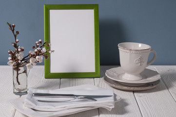 green picture frame  against blue wall on white wooden table and plate and spring flowers beside