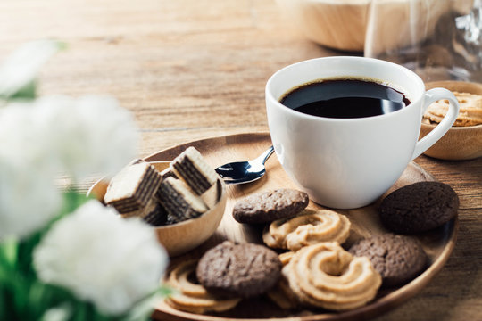 black coffee in white cup with cookie and dessert