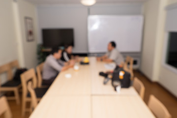 Corporate business team or student team and their adviser in meeting room, blurred background