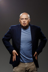 Close up portrait of handsome confident middle-aged businessman over black background.